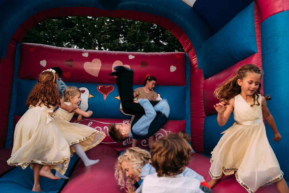 kids on bouncy castle, one in the centre is mid somersault