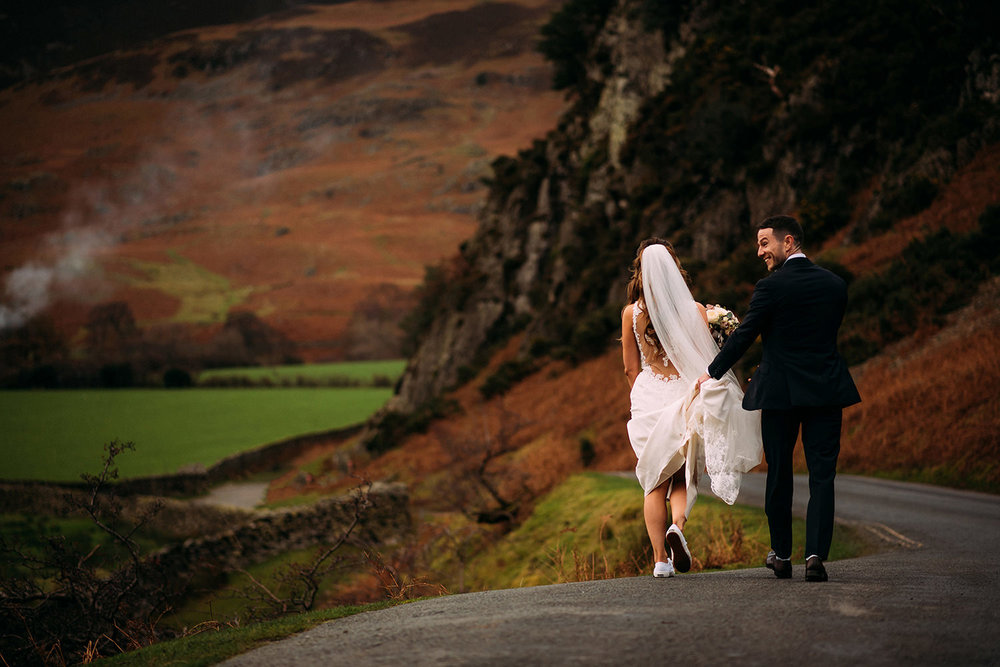 Bride and groom walking along the road by lake Buttermere
