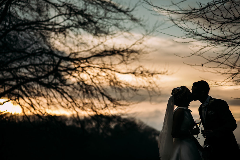 sunset silhouette of couple kissing at Mitton hall