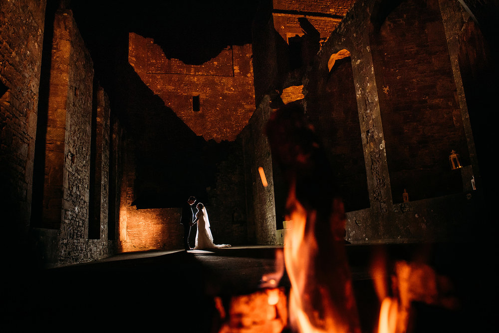 couple night time photo in Bolton castle with fire in the foreground