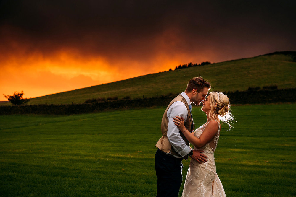 off camera flash photo of couple on Pendle hill with a red sky caused by on coming storm