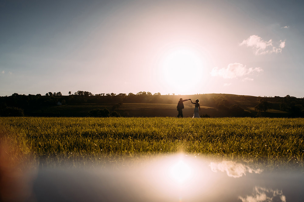 Bride and groom dancing in the sunset with reflection