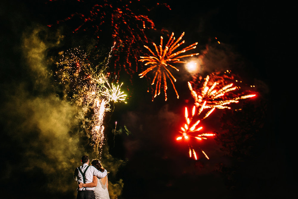 bride and groom under new years eve fireworks
