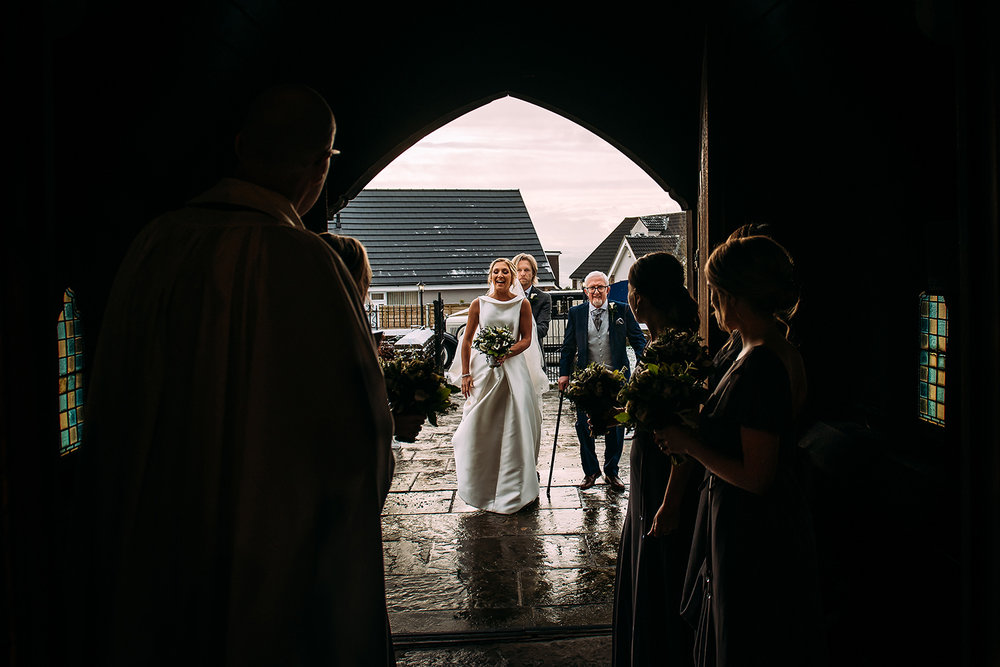bride and father walking up church path, shot through the church door