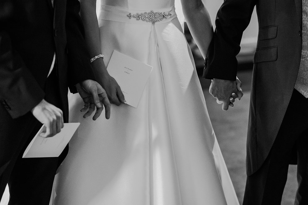 close up of groom and father of the bride holding the bride's hand. Can also see their names on the order of service. Black and white photo