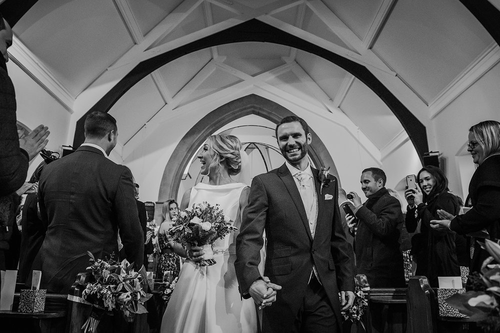 black and white photo of the the bride and groom leaving church