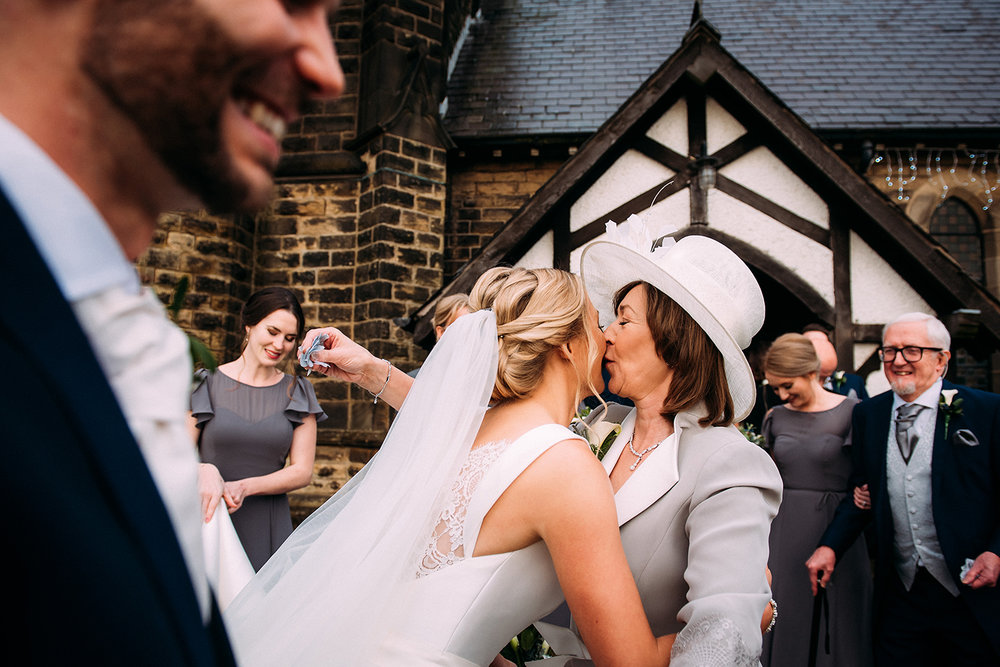 layered shot of bride and mother kissing, also has groom and bridesmaids in the foreground and background