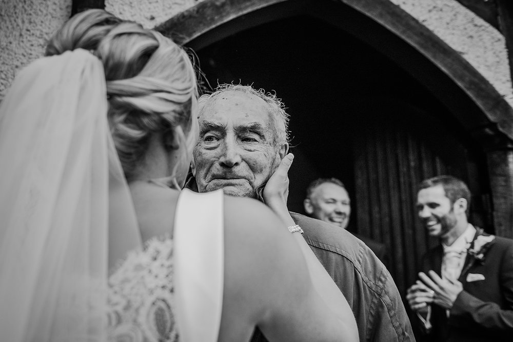 emotional black and white photo of the bride touching her grandfathers face