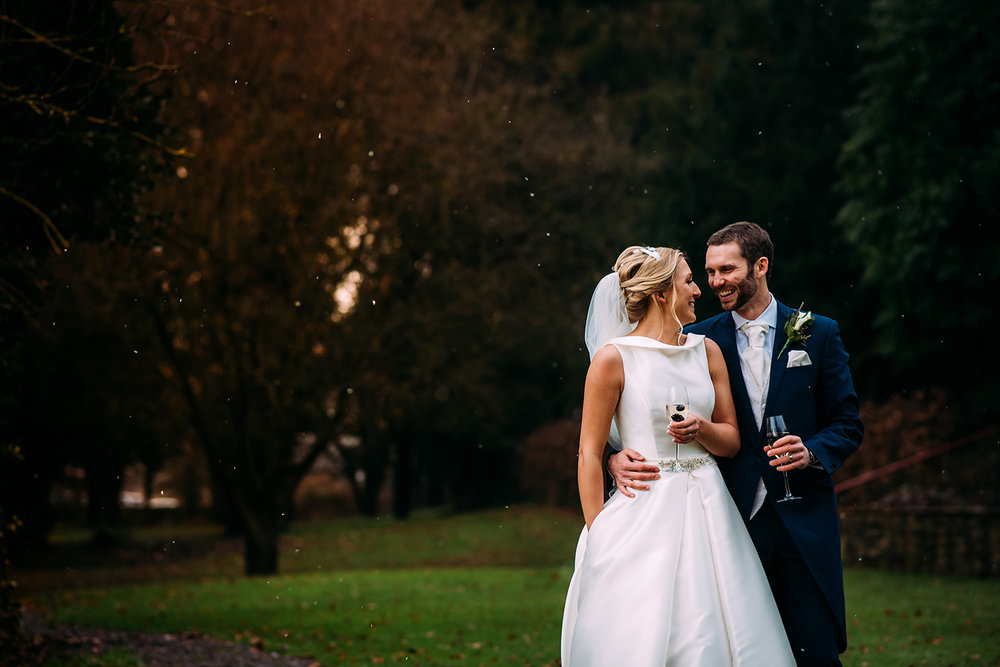 Bride and groom laugh in the grounds at Mitton hall