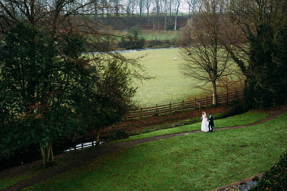 ariel shot of the bride and groom strolling the the grounds at Mitton hall