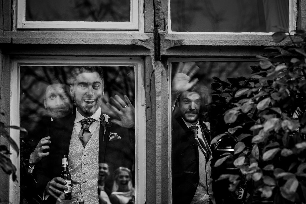 BW photo of guests laughing through the window with bride and grooms reflection