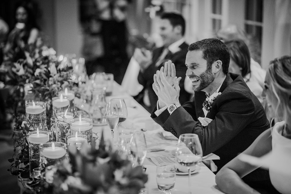 BW photo of groom during the speeches