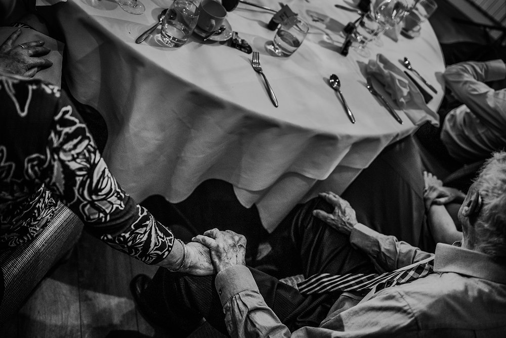 Black and white photo of the grandparents holding hands under the table during the speeches.