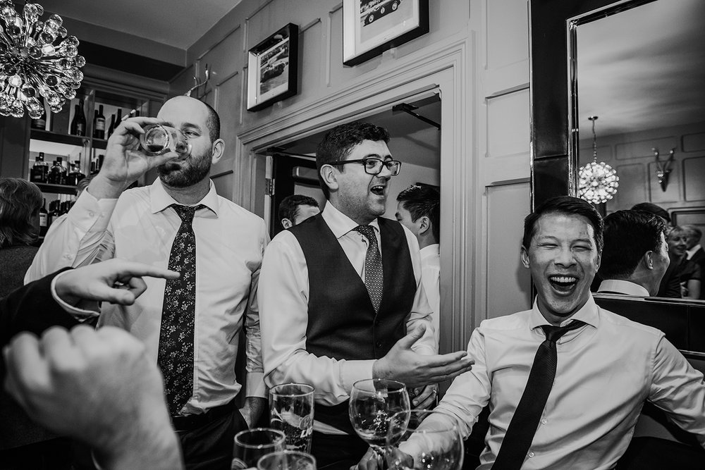 black and white photo of guests laughing and drinking