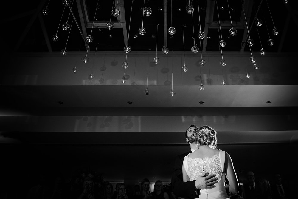 groom looks up at the sky during the first dance. BW photo