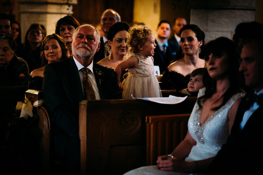 bride and grooms daughter being cheeky in church