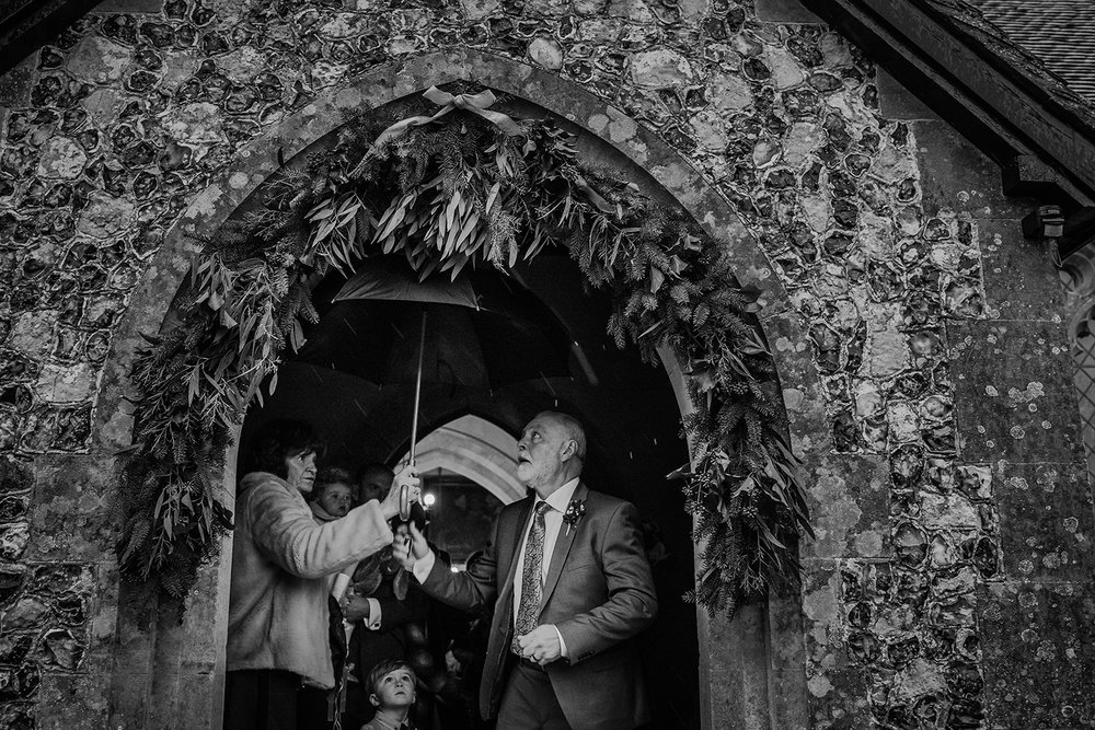 Father of the bride getting the umbrella up at the church door. BW photo