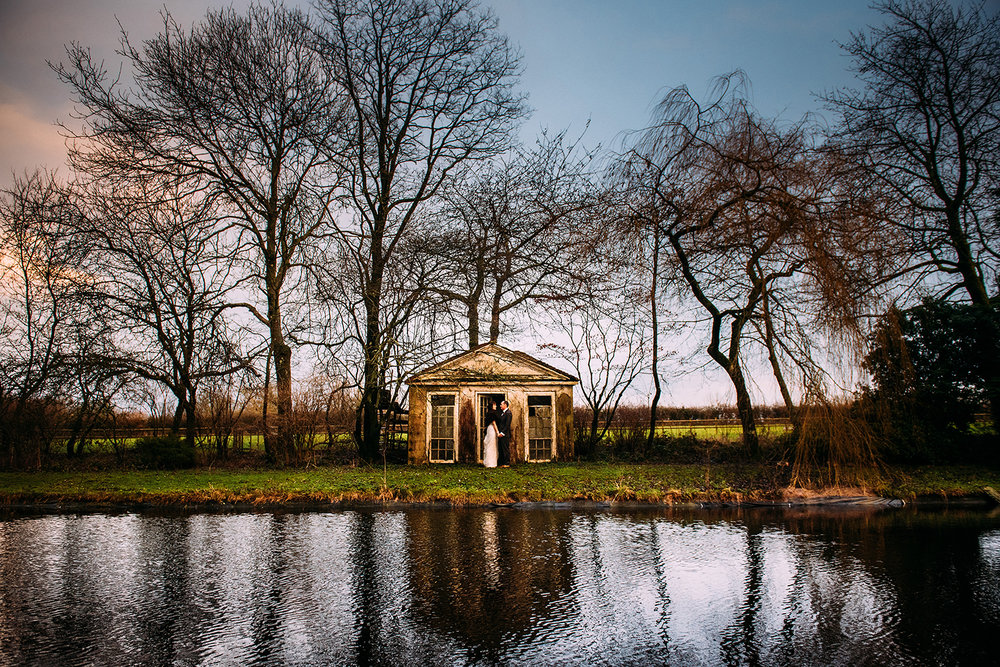 bride and groom by an old summer house by a pond
