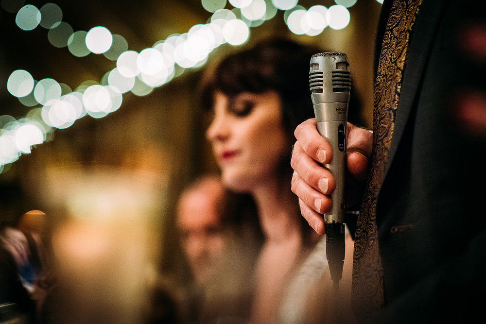 fathers hand holding microphone, bride in the background - soft focus