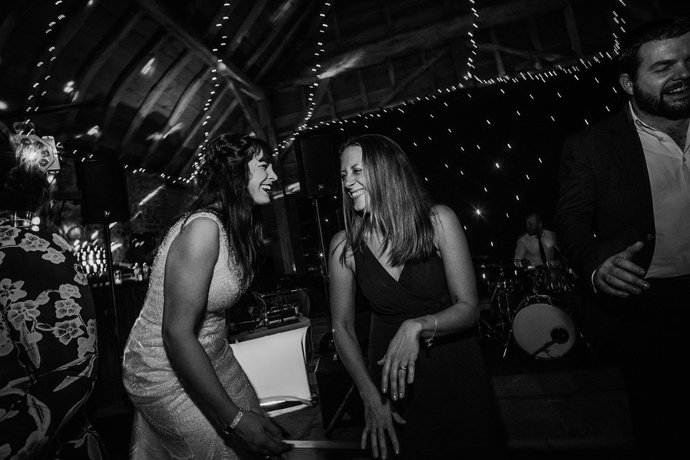 BW photo of bride laughing with friend