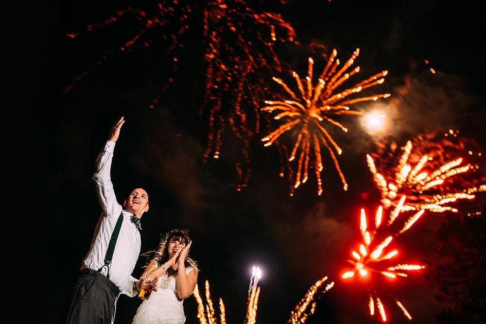 bride and groom waving at friends under NYE fireworks