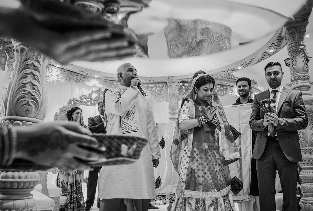 bw photo of bride praying while facing the guests