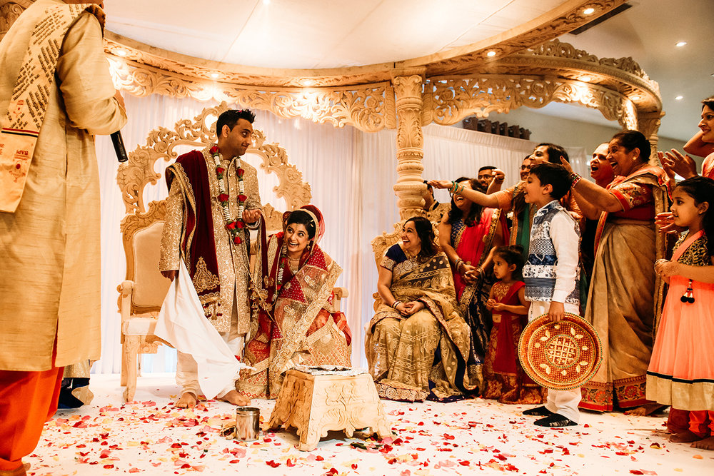 bride and groom laughing with family on the stage