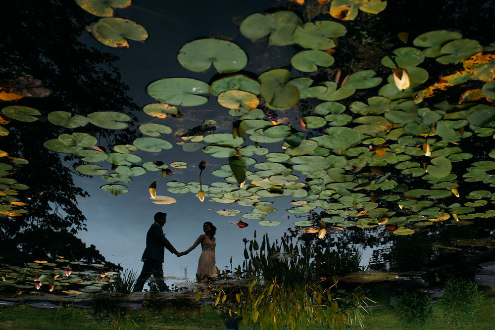 reflection of bride and groom in a pond