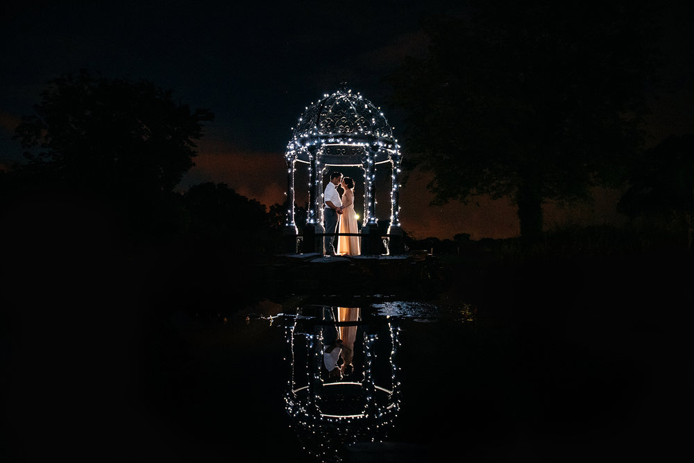 bride and groom together in a fairy lit gazebo at night with a reflection in the pond
