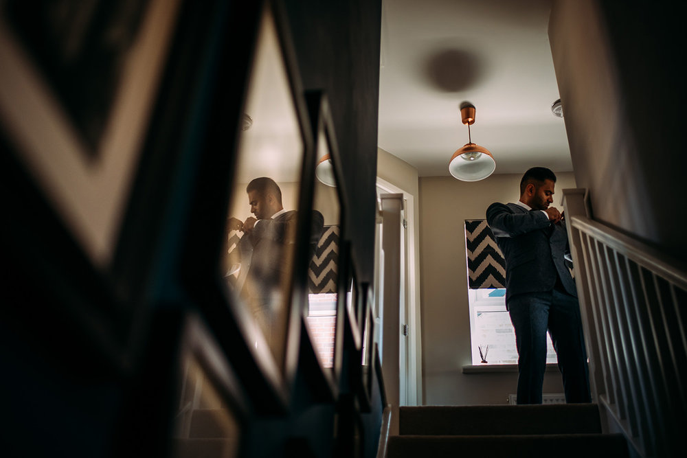 groomsman putting flower on jacket at the top of the stairs with a reflection in the picture frame