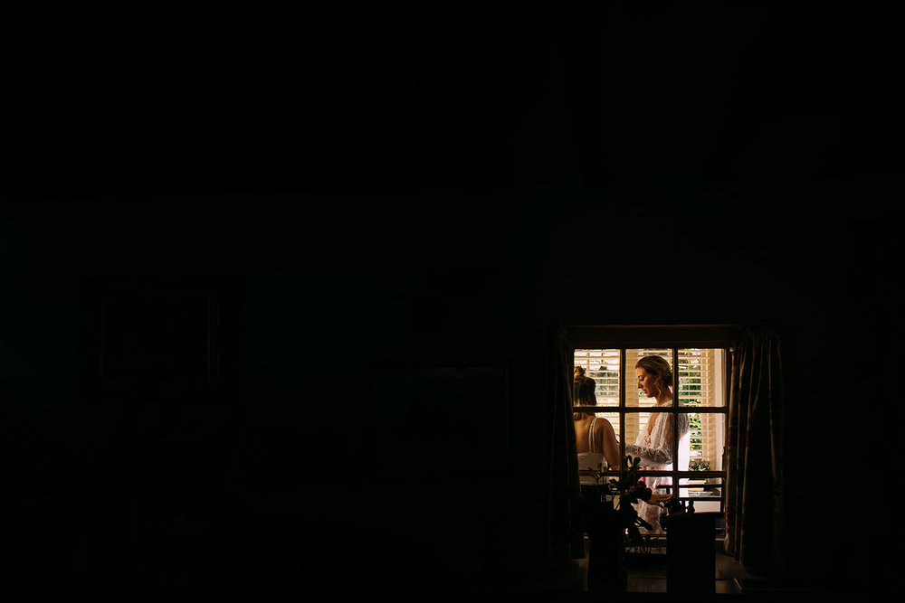 black image with a small frame of light in the bottom right corner of the bride in another room