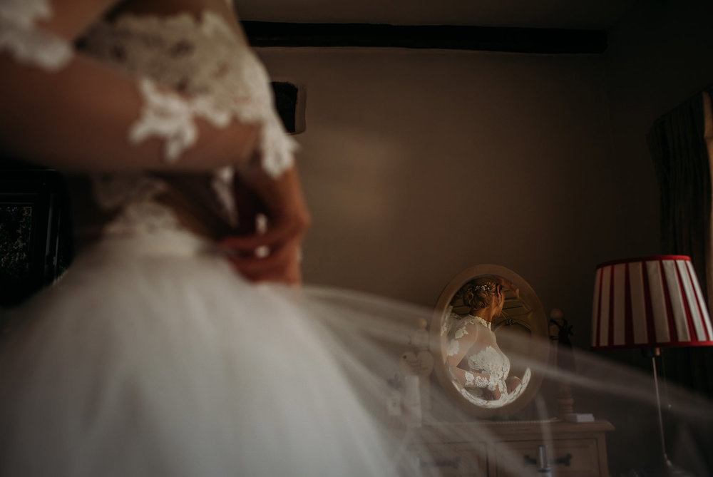 bride adjusting dress with the focus being a reflection in the distance