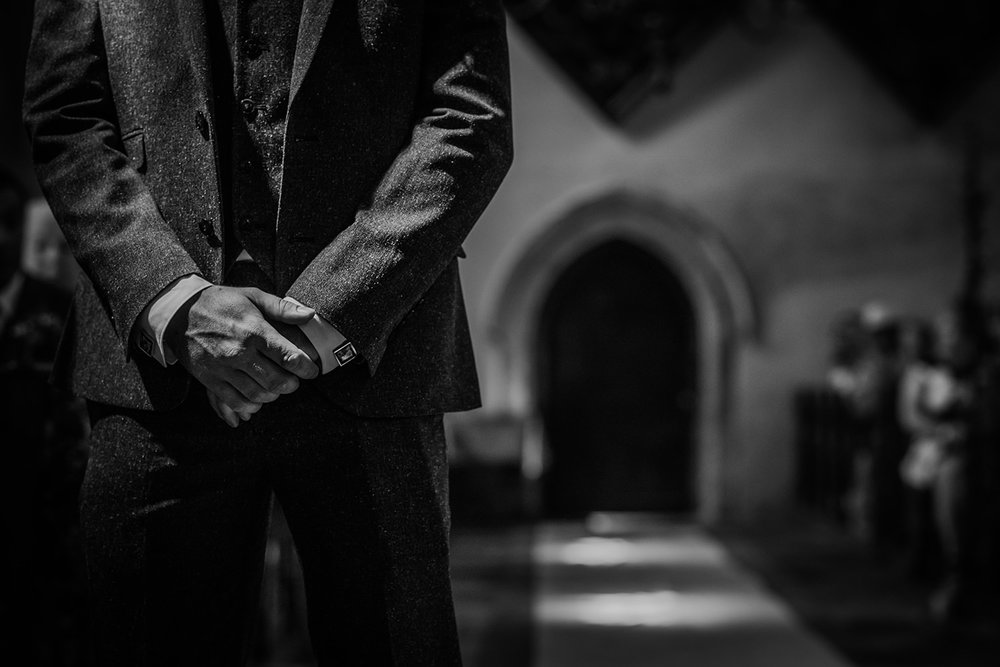 bw photo of the groom's hands as he waits