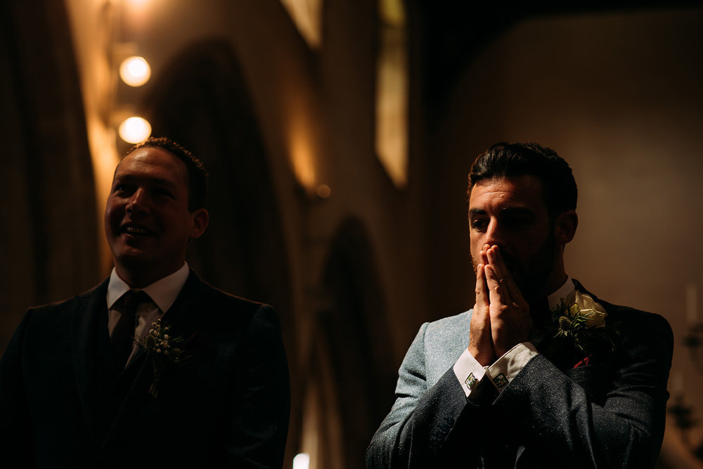 groom rubs his face nervously in strong light