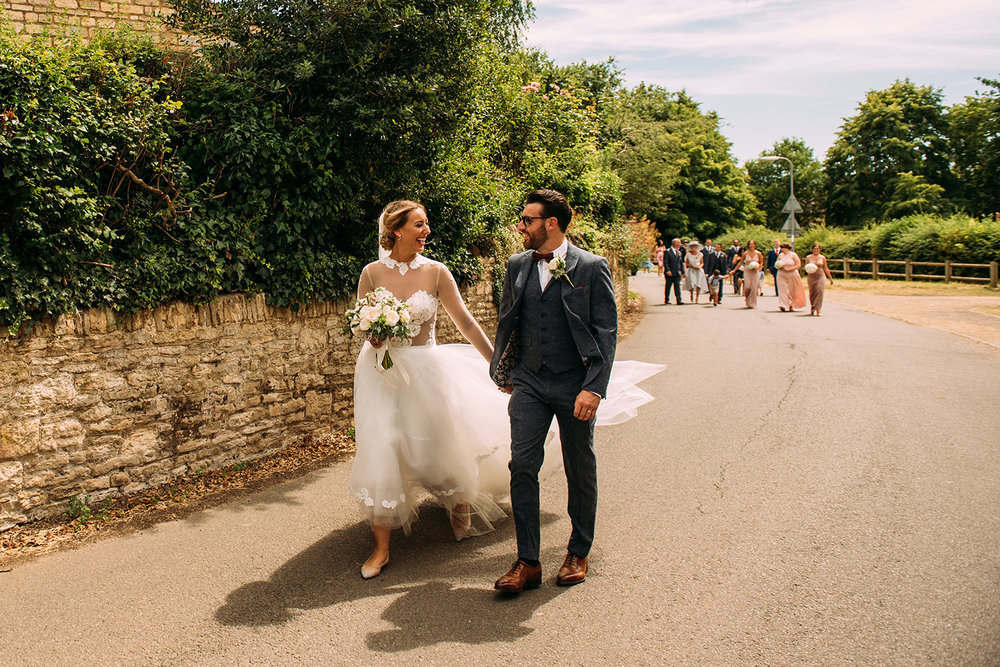 bride and groom walk through the village with their family in the distance