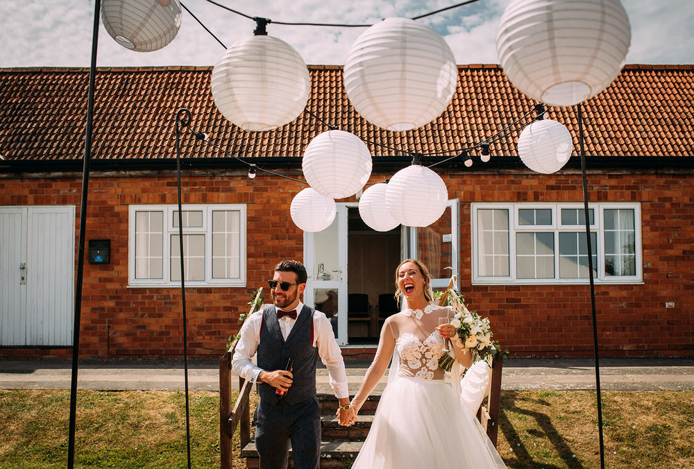bride and groom enter the reception marquee under lanterns