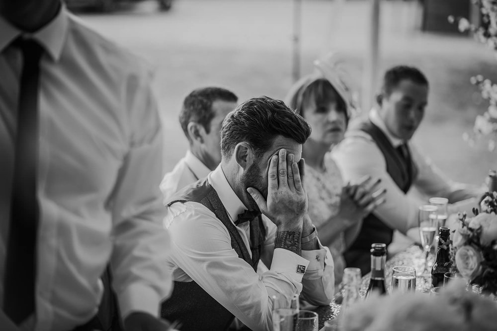bw photo, groom head in hands during the speeches
