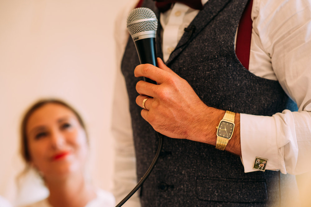 detail of grooms watch and microphone during the speeech with bride looking on in the background