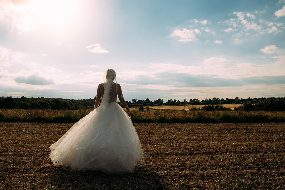 the bride walks into a field