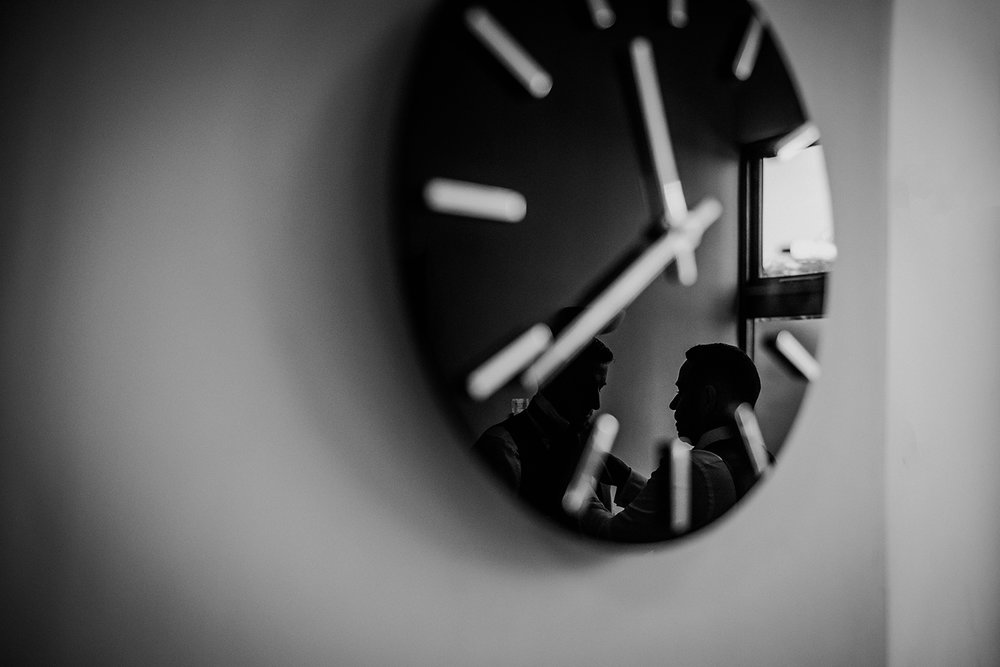Bw photo of a clock on the wall with a reflection of a groomsman helping the groom do his tie