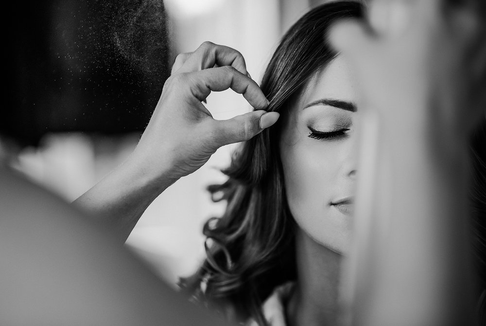 bw photo of half the brides face while her hair is sprayed