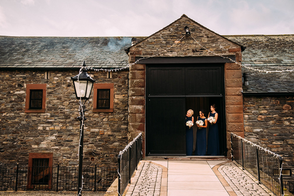bridesmaids peek out of new house farm door