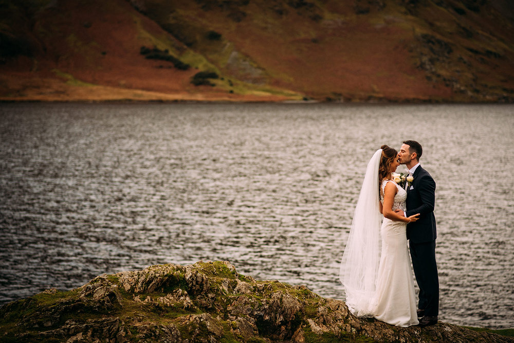groom kisses the brides forehead by the water