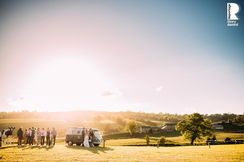 wedding guests mingle by the camper van in the distance at sunset