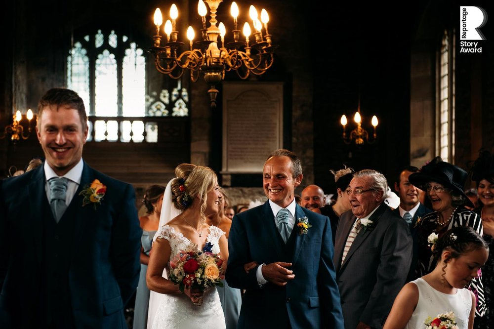 brides father prodly walks her down the aisle while she looks back and smiles at her grandfather