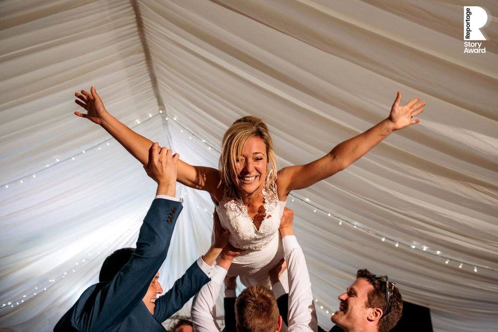 low angle of the bride being lifted during the first dance