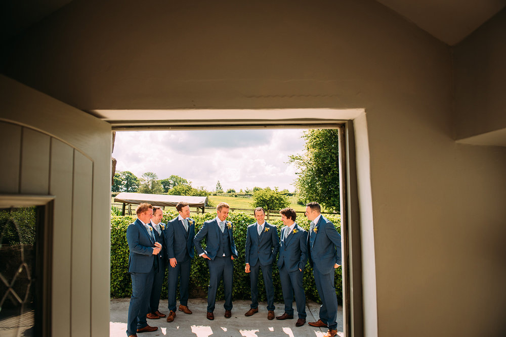 groom and groomsmen laughing in the doorway
