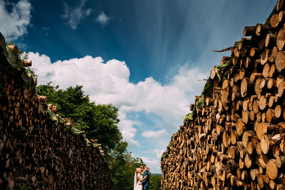 the couple kiss in between 2 huge log piles