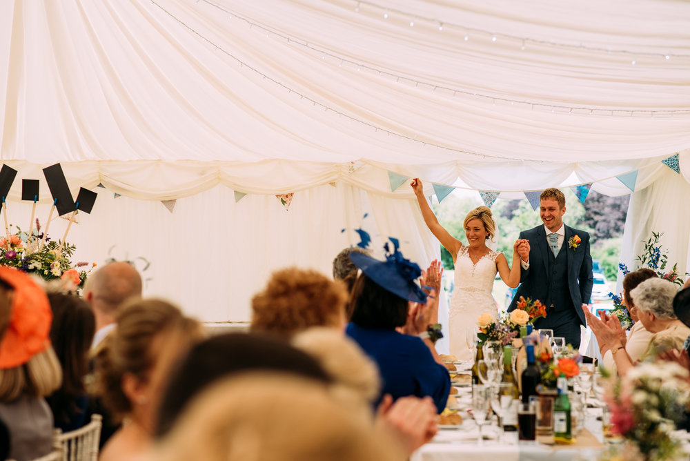 the bride and groom enter their wedding breakfast to huge cheer