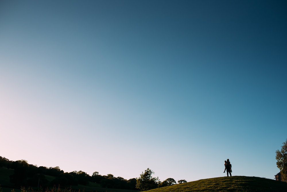 silhouette of the couple doing a 'piggyback' on a distant hill